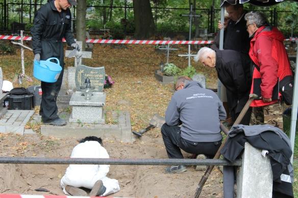 Prof. Krzysztof Szwagrzyk i sędzia Bogusław Nizieński w trakcie ekshumacji. W wykopie archeolog Justyna Sawicka (Fot. Marcin Maruszak)
